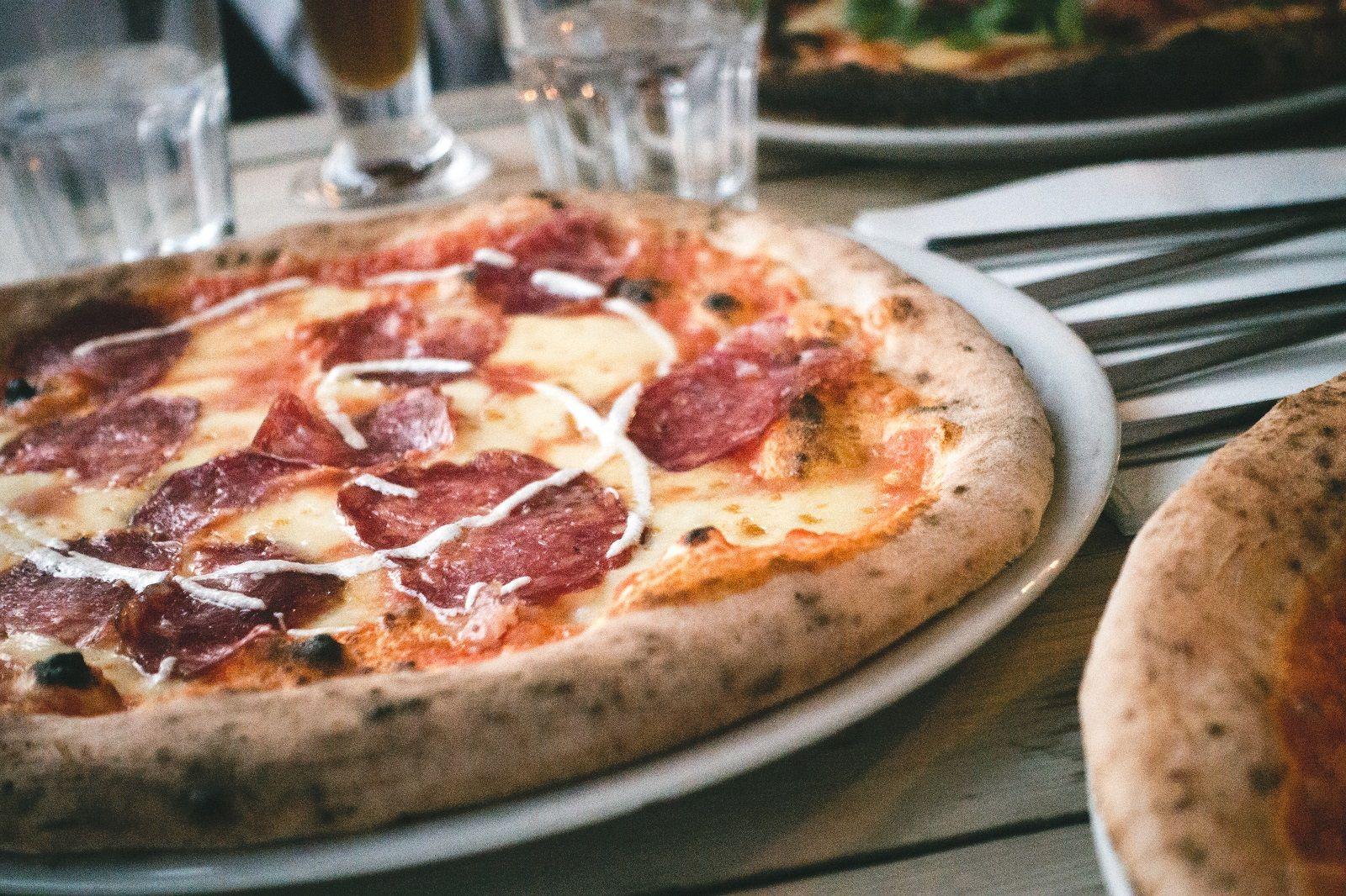 Okrúhla pizza so salámou a syrom, v pozadí poháre a príbory