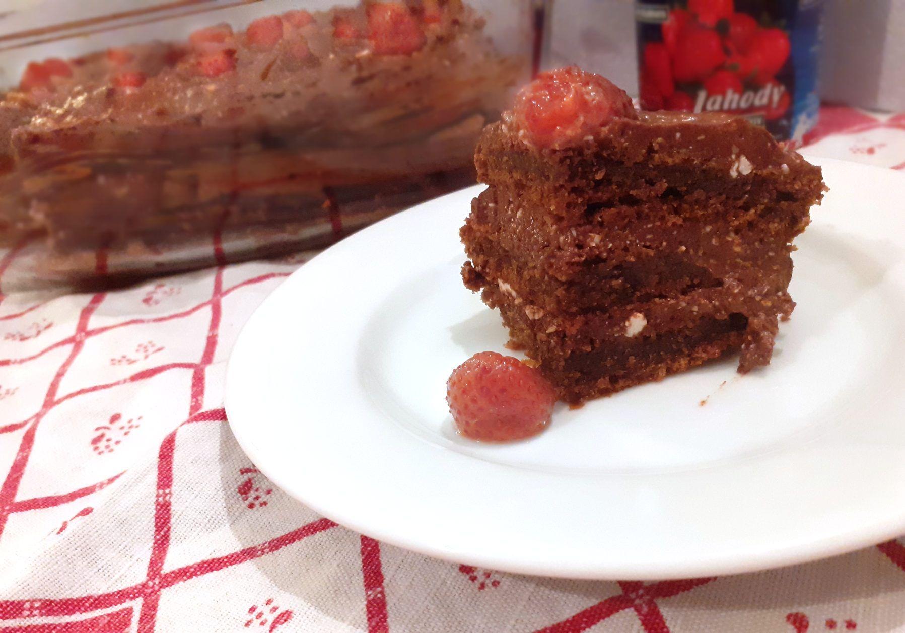 Kúsok čokoládovej torty s tvarohom a jahodou navrchu na tanieriku