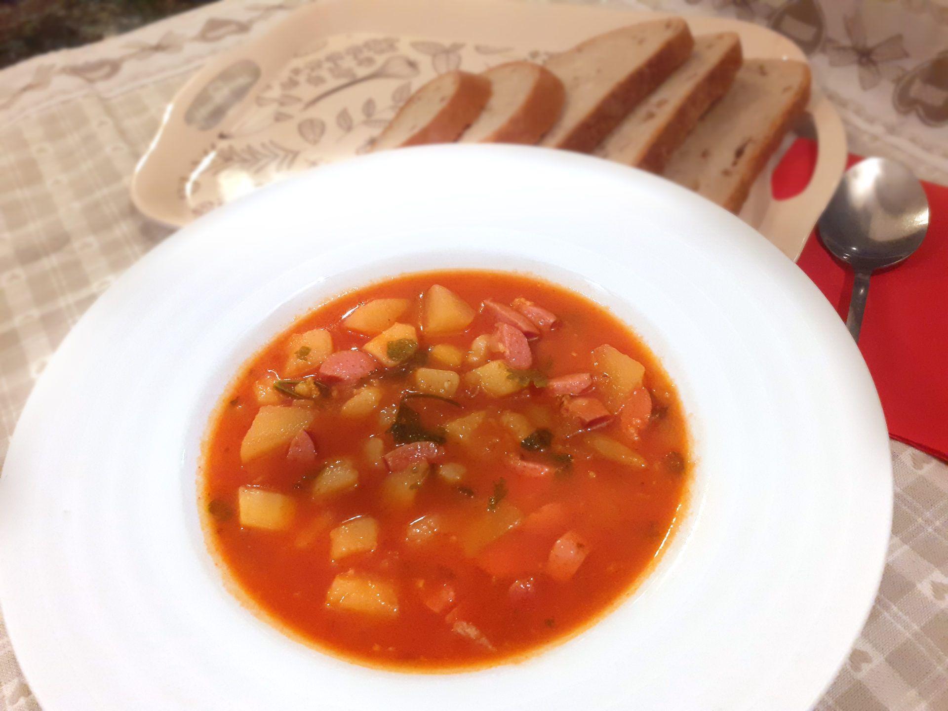 Hlboký tanier s paprikovou omáčkou, zemiakmi, párkami a vňaťou