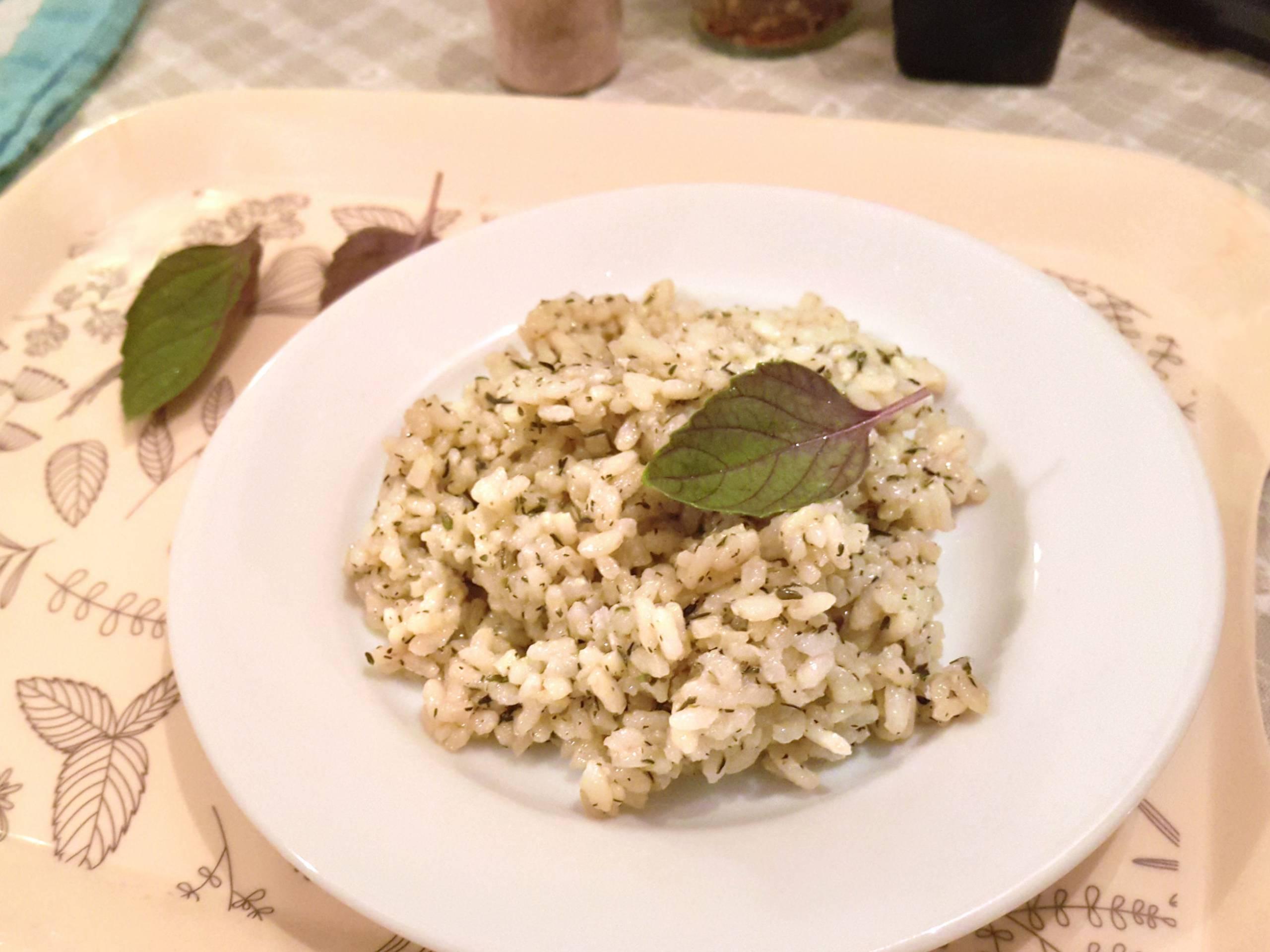 Domáca dusená ryža s tymianom na malom tanieri ozdobená bazalkou