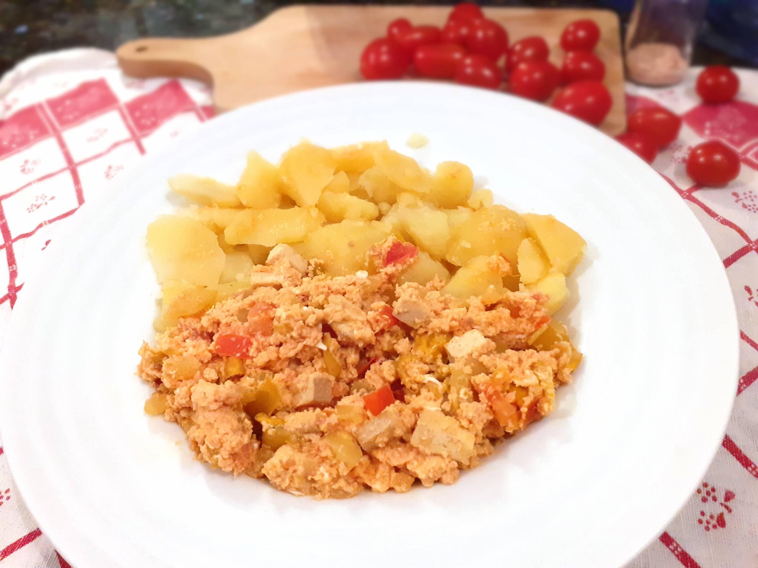 Lečo s tofu a varenými zemiakmi na tanieri v pozadí s cherry paradajkami