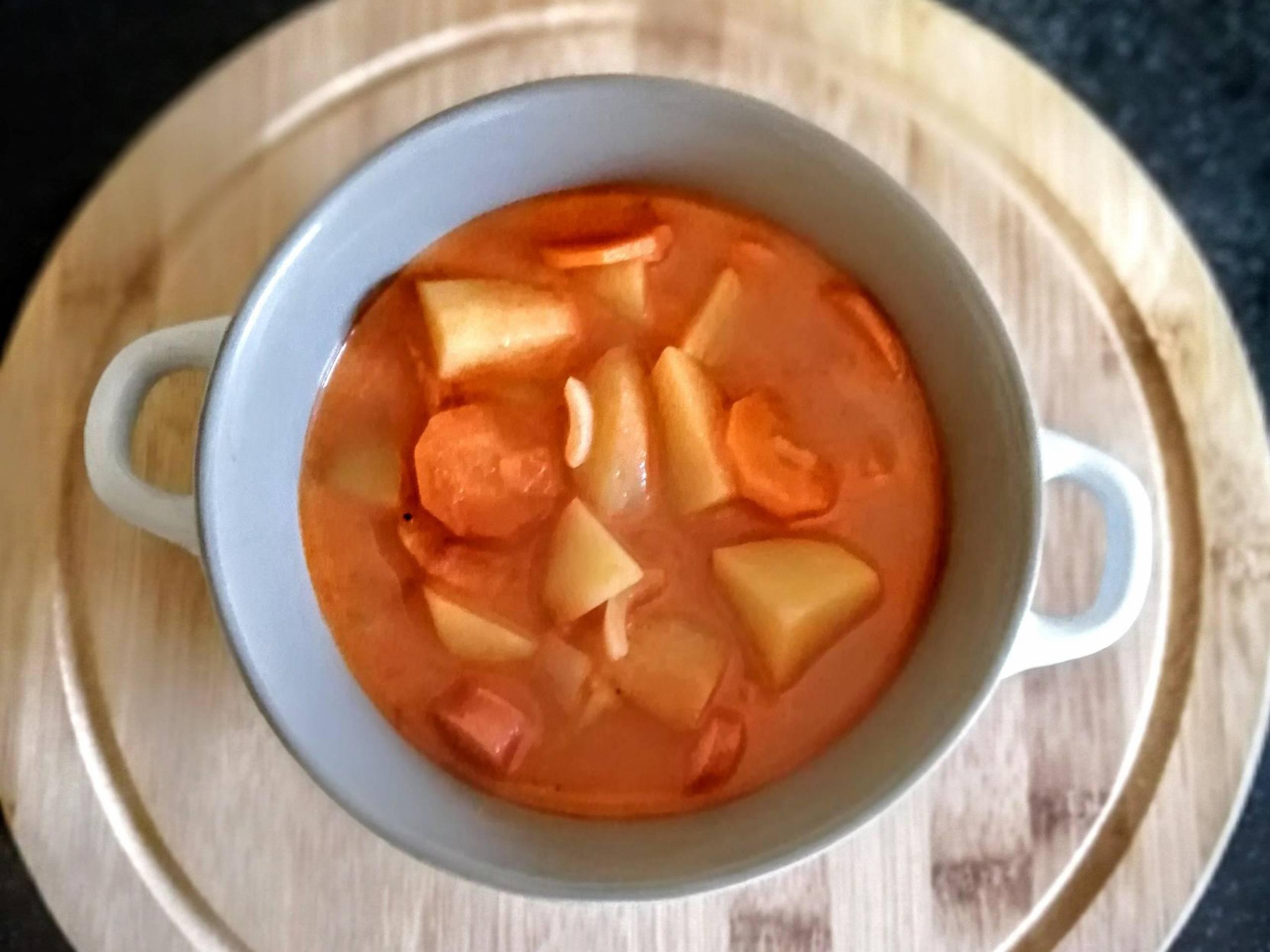 Gulášová polievka so zemiakmi a párky v hrnčeku s uškami na drevenej tácke