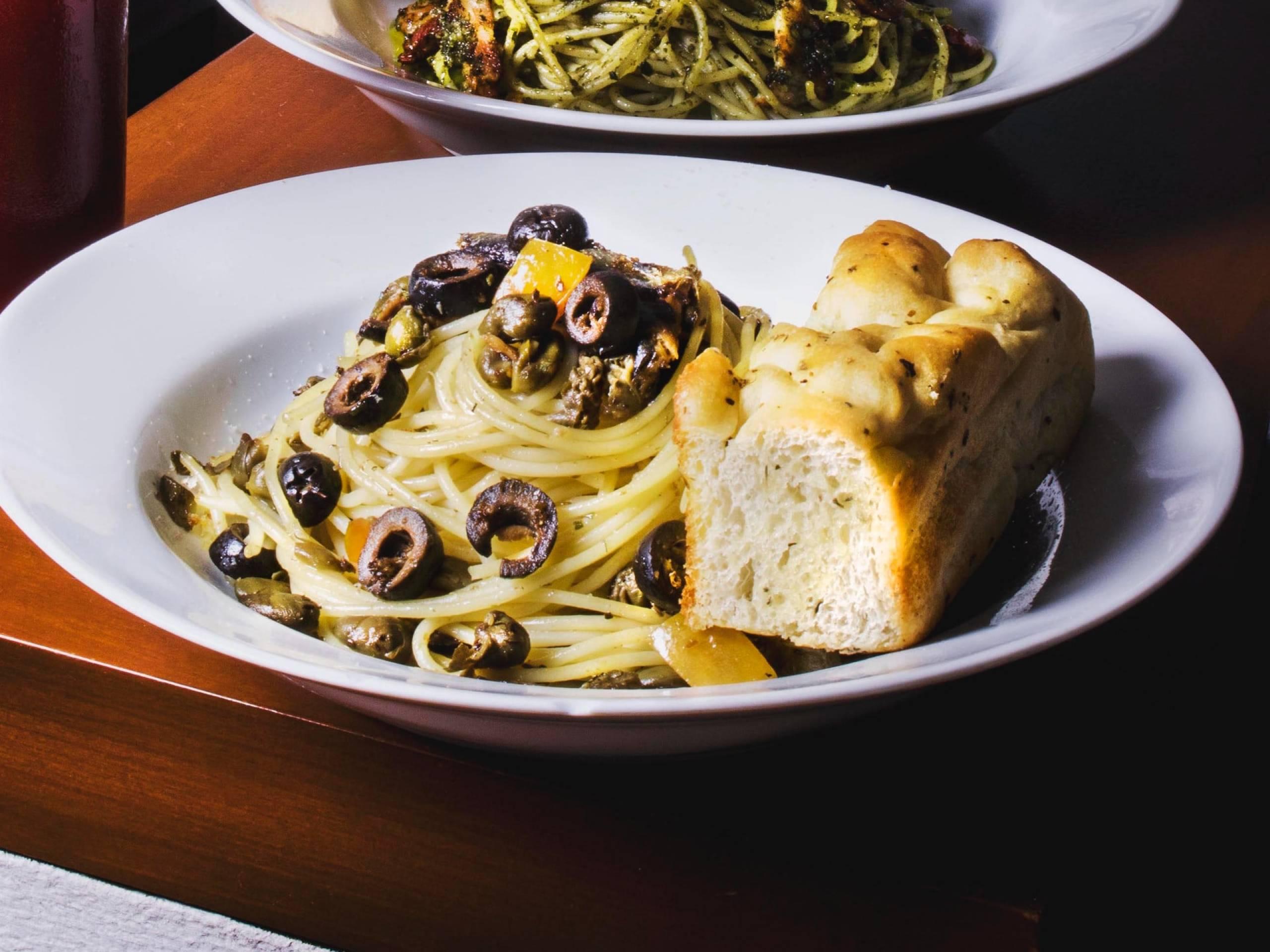 Cestoviny s čiernymi olivami a bagetkou na bielom tanieri